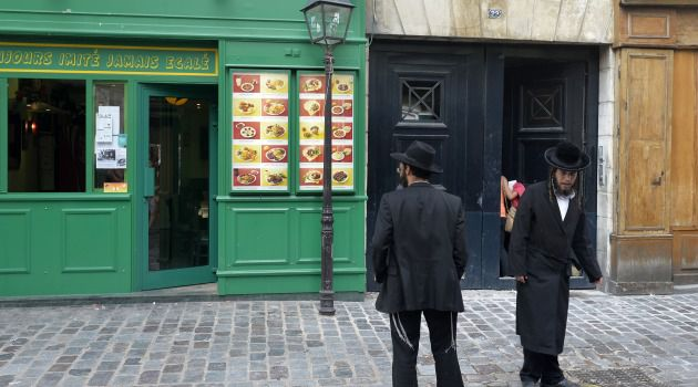 United in Memory: Hasidic men stand in the traditionally Jewish Marais neighborhood in Paris.