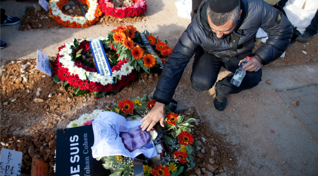 Cost of Mourning: A grief-stricken mourner touches a photo of one of the Paris terror victims at their funeral in Jerusalem.