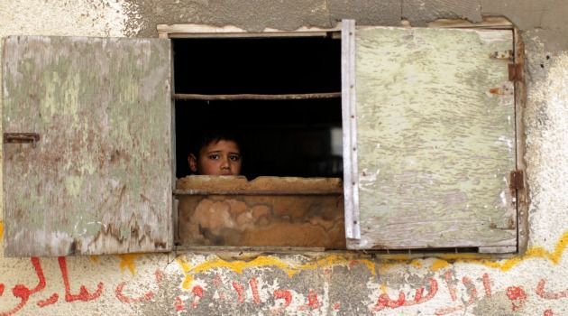 Harsh View: Palestinian boy peers out at funeral for Gaza militant killed by an Israeli strike.