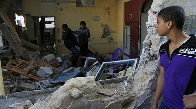 Major Damage: Palestinian children try to salvage items from wreckage of building hit by Israeli air strike.