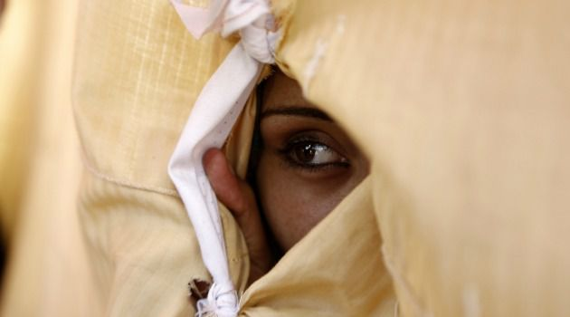Eye of the Storm: A Palestinian woman looks on through a hole in a sheet which covers her improvised tent in Gaza City.