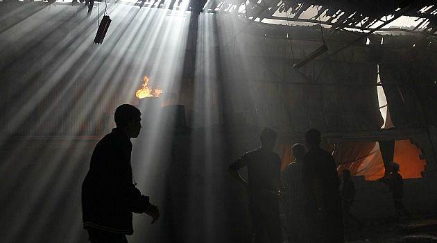 Damaging Fire: Palestinian rescue workers douse a fire in a factory hit by Israeli airstrikes.