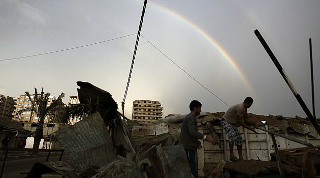 Uneasy Peace: Framed by rainbow, Gaza residents pick through rubble of destroyed building.