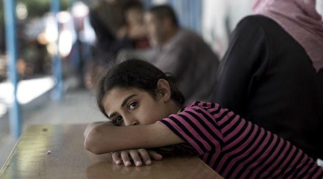 Palestinian girl rests after UN-run shelter was hit by Israeli attack.