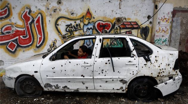Palestinian boy plays in shrapnel-riddled car as a truce with Israel held for a second day in Gaza.