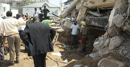 African Disaster: Bystanders gather around the rubble of a collapsed department store in Ghana?s capital of Accra.