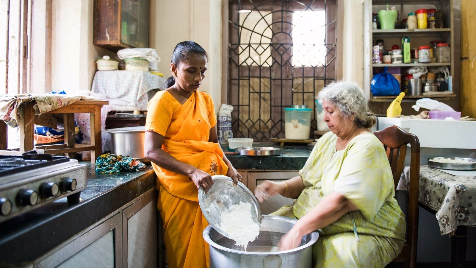 Suneka (left) adds 'chick' (wheat gluten) to coconut milk to make Sharona Hayeems's sweet milk custard called halwa.