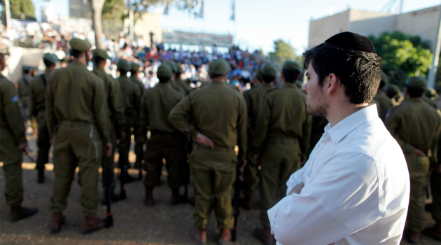 Share the Burded: An ultra-Orthodox Jew watches a military graduation parade. Israel?s coalition reached a deal to phase out the the exemption from national service for Haredi youth.