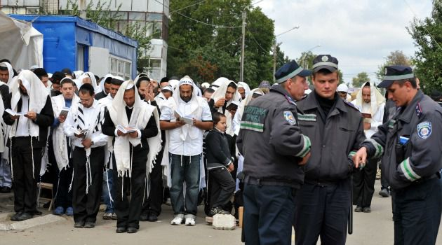 Keeping Watch: Ukrainian police stand guard as Hasidim pray in Ukrainian town of Uman. The annual pilgrimage to Jews is seen as a mixed blessing by some locals.
