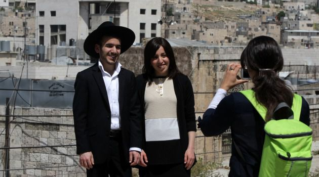 Smile, You Got a Subsidy : Jewish settlers pose for pictures in the Palestinian town of Hebron. Israeli lawmakers are increasingly questioning th high cost of Jewish settlements on the West Bank.