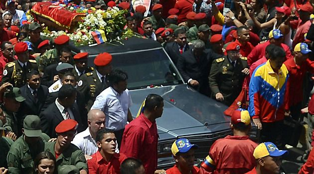 Emotional Outpouring: Crowds gather as the body of Hugo Chavez is carried in a hearse through the streets of Caracas.