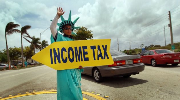 Pay Up: A man holds a sign reminding Americans to file their taxes before the IRS deadline.