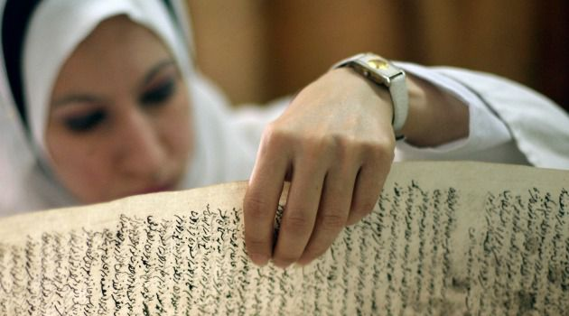 Echoes of Lost Civilization: An Iraqi employee examines a document in the Jewish archives in Baghdad. Should the collection stay in the U.S., or be returned to its homeland?