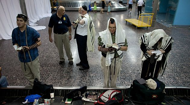 Arrival Prayer: Immigrants pray in the terminal at Israel?s Ben Gurion airport.