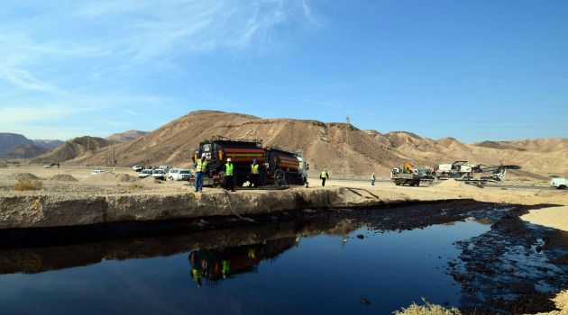 Desert Damage: Israeli workers examine pool of oil as they assess damage from nation's worst-ever pipeline break near Eilat.