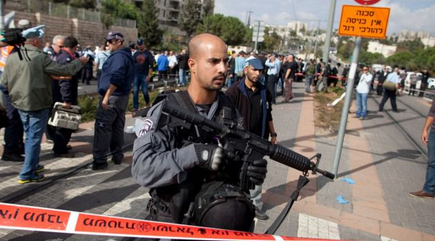 Israeli soldier guards scene of a suspected terror attack in which a Palestinian driver rammed into pedestrians at a Jerusalem light rail station.