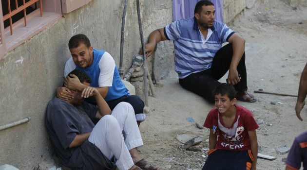 Under Fire: Palestinians sitting on a street react after a deadly Israeli air strike that targeted their house in the town of Khan Yunis in the Gaza Strip.