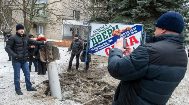 Residents in eastern Ukraine town of Kramatorsk pose next to unexploded missile.