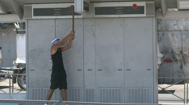 Mad as Hell : Enraged Palestinian protester uses a pick-axe to damage Jerusalem light-rail station.