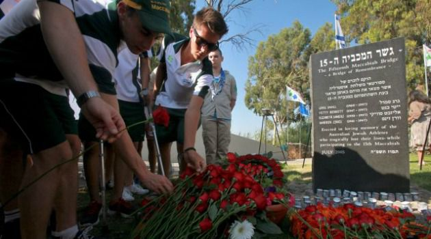 Who?s Responsible? Mourners place flowers on grave of those killed in the 1997 bridge collapse at the Maccabiah Games in Australia.