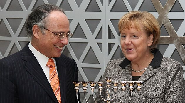 Light of Tolerance: German Chancellor receives a menorah from central council of German Jews leader Dieter Graumann after speaking at a gathering of the Jewish group.