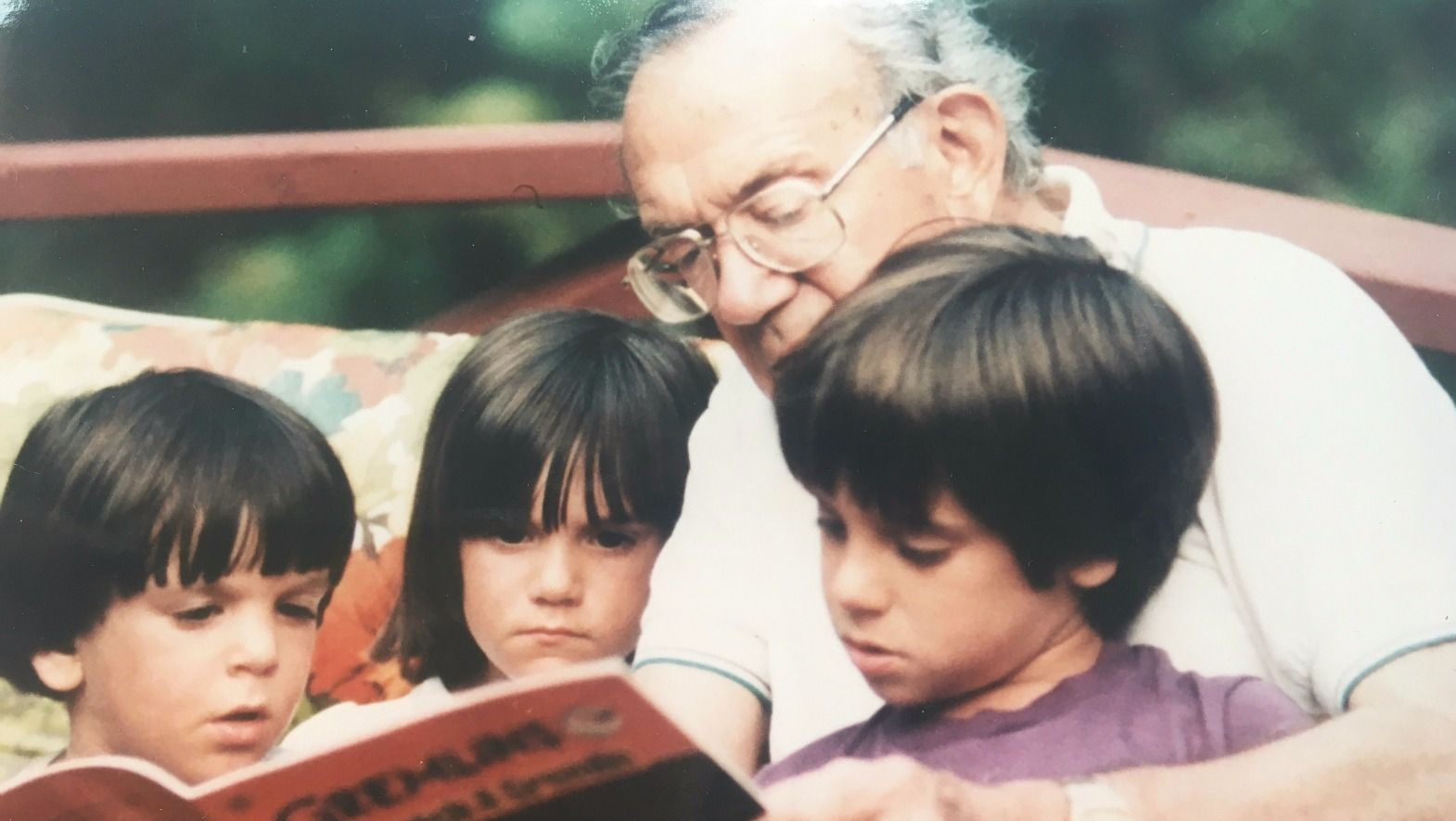 Story Time: Morris Paley reading to his grandchildren, brothers Danny (left) and Brett Nidel (right) and their cousin Megan Hart.