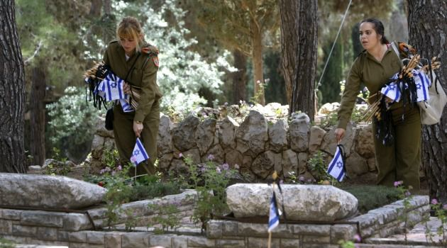Israeli soldiers place the national flag on graves of killed comrades at the Mount Herzl military cemetery in Jerusalem.