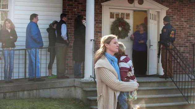 A woman holds a child near the the scene of an elementary school shooting in Newtown, Connecticut.