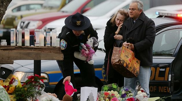 Town of Tears: Newtown residents leave flowers outside the Sandy Hook school where a gunman went on a deadly shooting rampage.