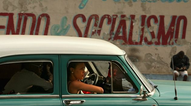 Isolated: Cubans ride in one of the period American cars that are a staple of transportation on the island.