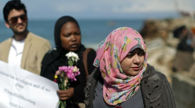 Tears and Flowers: Palestinians toss flowers into the Mediterranean Sea to mourn the murders of three Palestinian-Americans in North Carolina.