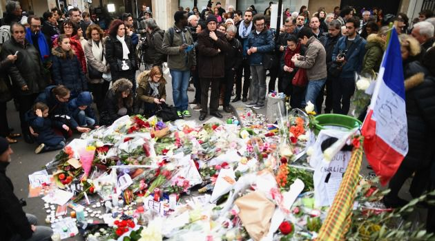 Nation Grieves: Crowds gather around a makeshift memorial to the victims of the terror attack on a Paris kosher grocery store and the earlier attack on Charlie Hebdo magazine.