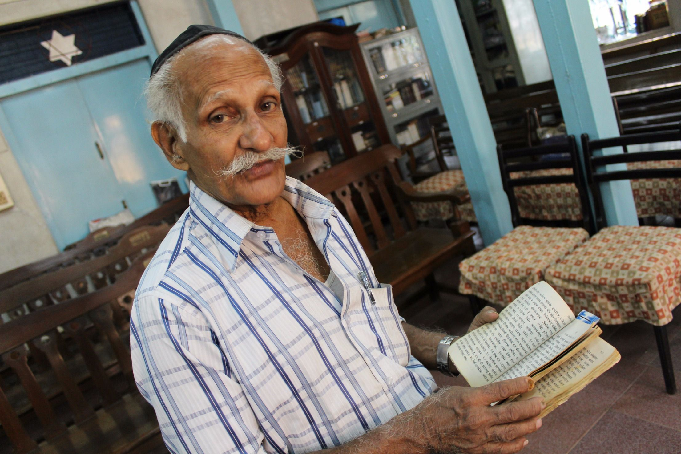People of the Book: Solomon Penkar, the caretaker of Tiferet Israel synagogue, pages through a Psalms book in Marathi, one of India's official languages.