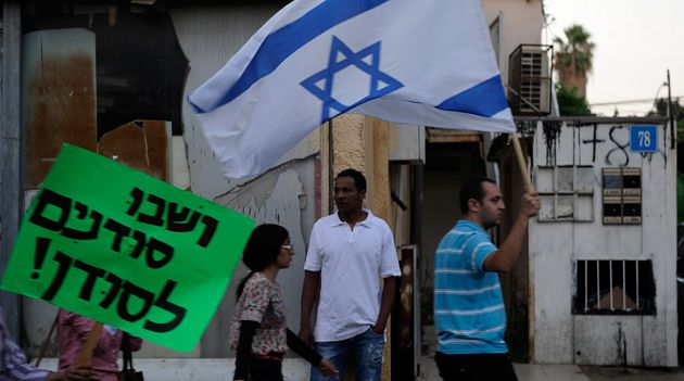 An African migrant stands as a right-wing protestors walk past holding Israeli flags and banners during a demonstration against African migrants in Tel Aviv on May 30, 2012.