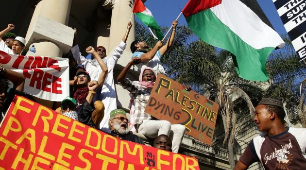 Pre-Pig Head: Demonstrators hold Palestinian flags and banners during a protest against Israel's military operations in Gaza.