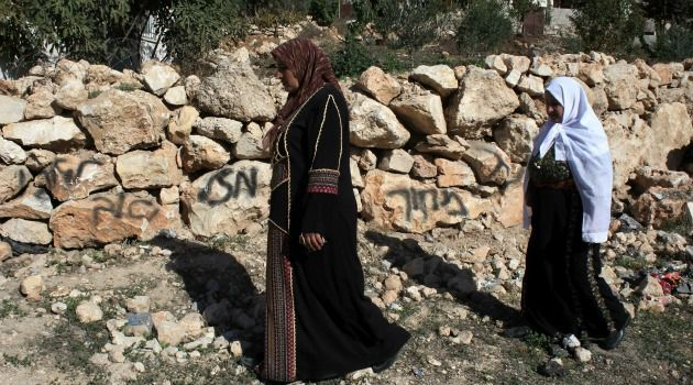 Price Tag Attack: Palestinian women walk by graffiti carried out by extremist Jewish settlers on the West Bank.