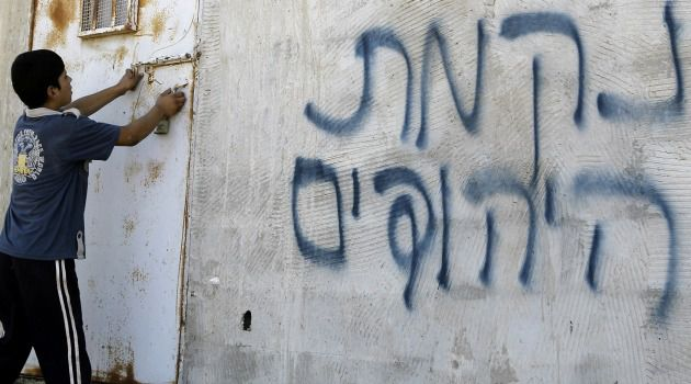Deja Vu? A Palestinian boy opens a door after Hebrew graffiti was daubed on a wall, allegedly by Jewish settlers, in the West Bank on July 2, 2014.