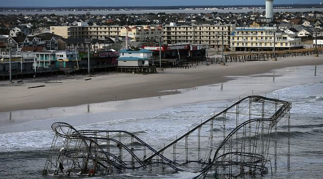 The wreckage of a roller coaster sits in the Atlantic Ocean in the Jersey Shore. In New York, some subways started to run but power was still out for much of lower Manhattan.