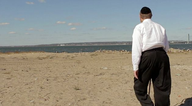 Still the Same: Pinny Dembitzer walks along the Atlantic Ocean in the Sea Gate section of Coney Island. A year after Sandy struck, the neighborhood is as unprotected as ever, but the reasons for its continued exposure are surprising.