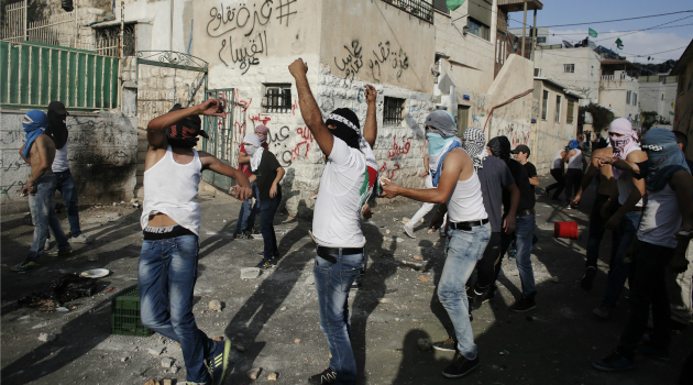 Palestinian youth hurl stones at Israeli policemen during a protest against the death of Muhammad Abd Al-Majid Sunuqrut in East Jerusalem.