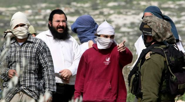 Jewish settlers square off against an Israeli soldier near the Palestinian village of Farata on the West Bank.