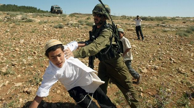 Cracking Down: Israeli soldier confronts a young settler trying to attack Palestinian farmers on the West Bank.