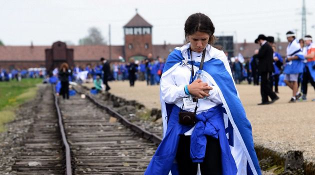 Don't Forget: A woman participates in the March of the Living at Auschwitz. Grassroots Polish communities are coming up with new and innovative ways of remembering the Shoah.