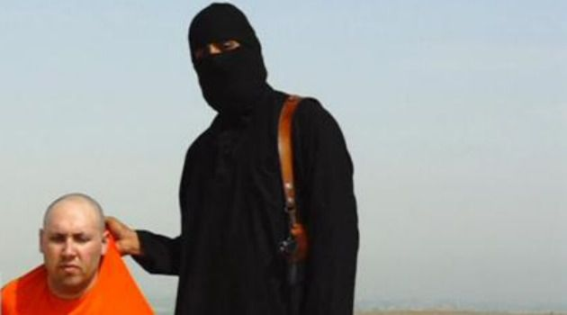 A masked Islamic State militant speaks next to a man purported to be U.S. journalist Steven Sotloff at an unknown location in this still image from an undated video posted on a social media website.