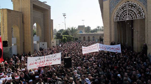 Thousands of Sunni Muslim protestors hold banners and wave their national flag during a demonstration on January 4, 2013 criticising Iraq?s premier and demanding the release of prisoners they say are wronglfully held, near Abu Hanifa mosque, in the mostly Sunni Muslim neighbourhood of Aldhamiya in Baghdad.