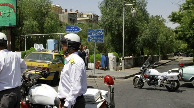 End Near? Syrian police guard road where bombers struck, killing several members of President Assad?s inner circle.