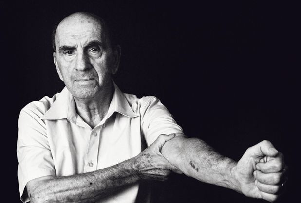 A Holocaust survivor displays tattoo Nazis inked on his arm.