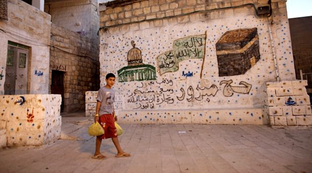 Property Dispute: A Palestinian boy walks past a building in East Jerusalem that was recently purchased by Israeli settlers.