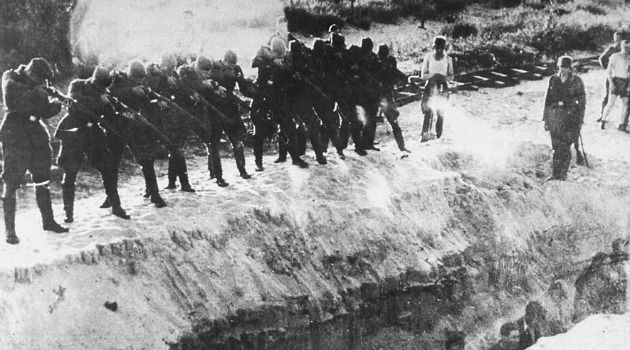 Places of Slaughter: Members of a Nazi unit firing at men standing at the bottom of a trench.