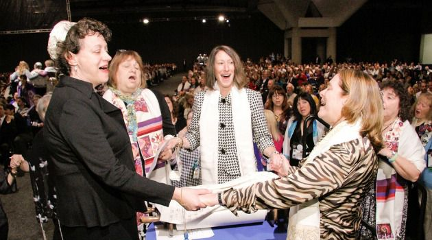 Reform Renewal: A group of women hold hands around the Torah during the Shabbat morning service at the Union for Reform Judaism?s biennial conference in San Diego.